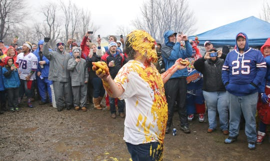 Ken Johnson of Rochester, a software engineer, is squirted with mustard and ketchup at a ritual tailgate party before the Bills game against the Dallas Cowboys in January 2016. A fan survey is asking how important is tailgating at games to fans and would the culture be lost at a new downtown stadium?