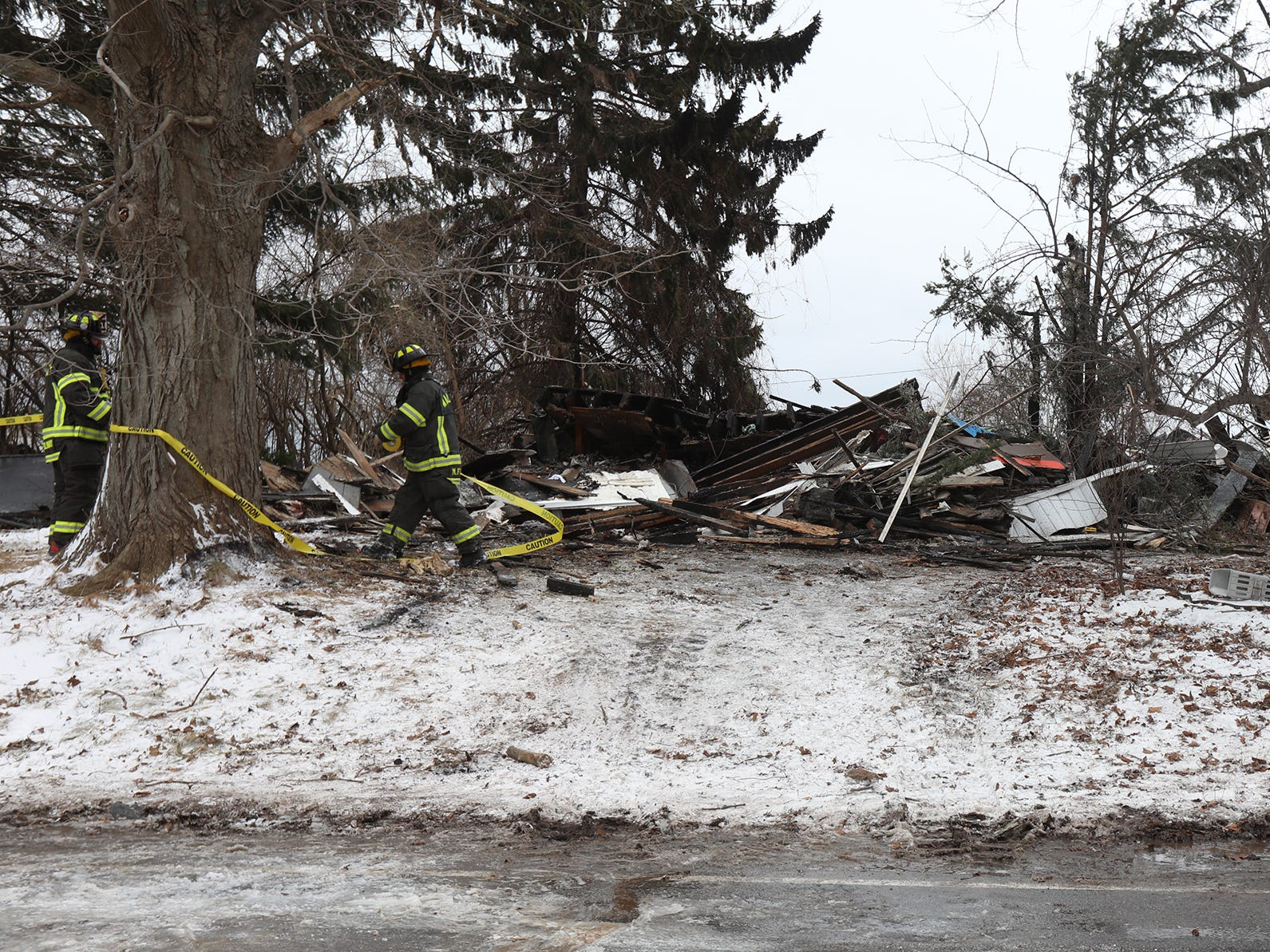 Firefighters put up a caution tape around the destroyed house.