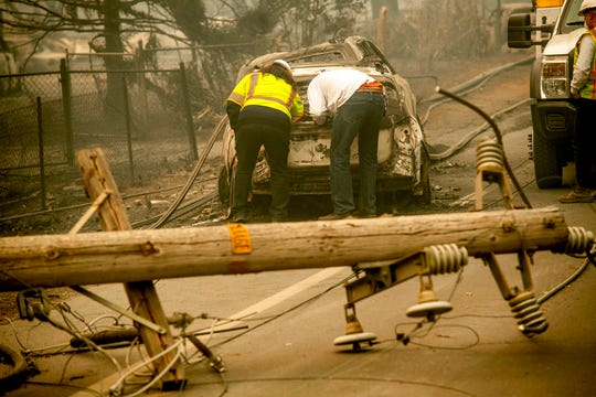 In this Nov. 10, 2018, file photo, with a downed power utility pole in the foreground, Eric England, right, searches through a friend's vehicle after the wildfire burned through Paradise, Calif. To prevent wildfires, Pacific Gas & Electric Co. should re-inspect its entire electric grid and cut off power during certain wind conditions regardless of the inconvenience to customers or loss of profit, a U.S. judge proposed Wednesday, Jan. 9, 2019.