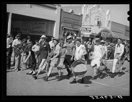 A brick-paved Chadbourne Street is seen in this photograph by Russell Lee, taken during the Fat Stock Show and Rodeo Parade of 1940.