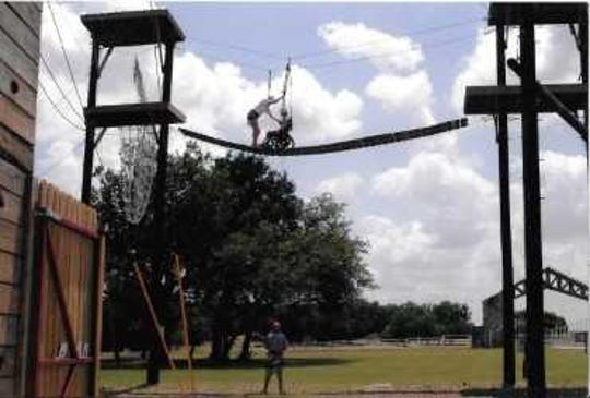 A child being helped along a ropes course plank at Camp John Marc in Meridian, Texas.