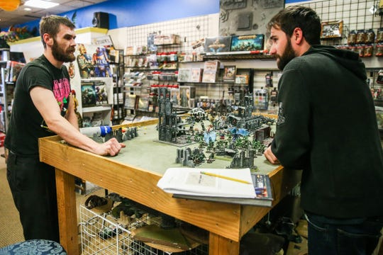 Sean Day, left, and Chris Morise play Warhammer 40,000, a tabletop strategy game Thursday, Jan. 10, 2019, at Specialties Games Toys & Gifts.