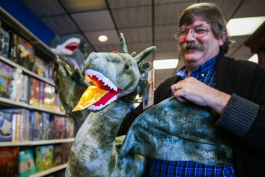 George Bell turns on the light on a dragon toy Thursday, Jan. 10, 2019, at Specialties Games Toys & Gifts.