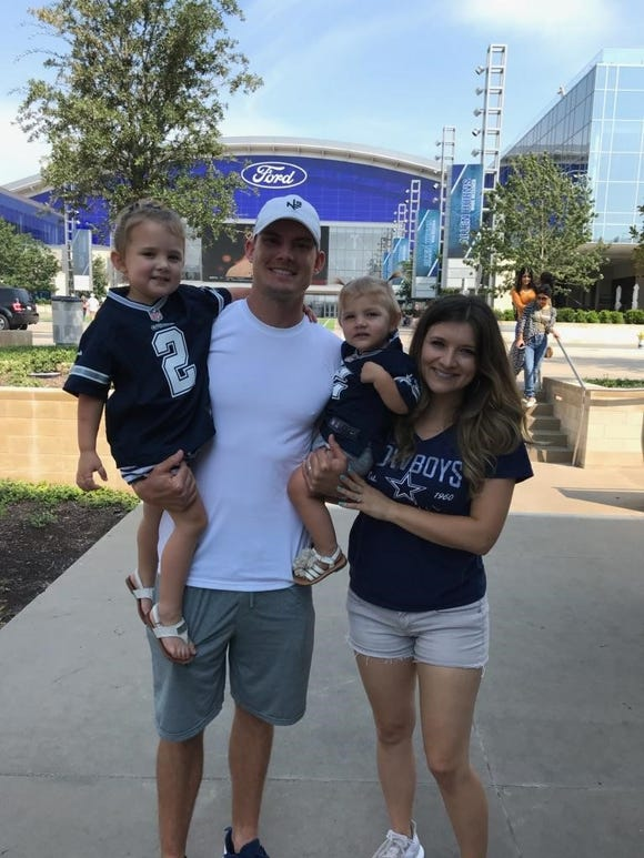 Brett Maher poses in front of AT&T Stadium in Dallas with his his wife, Jenna, and daughters Maela (left) and Laekyn.