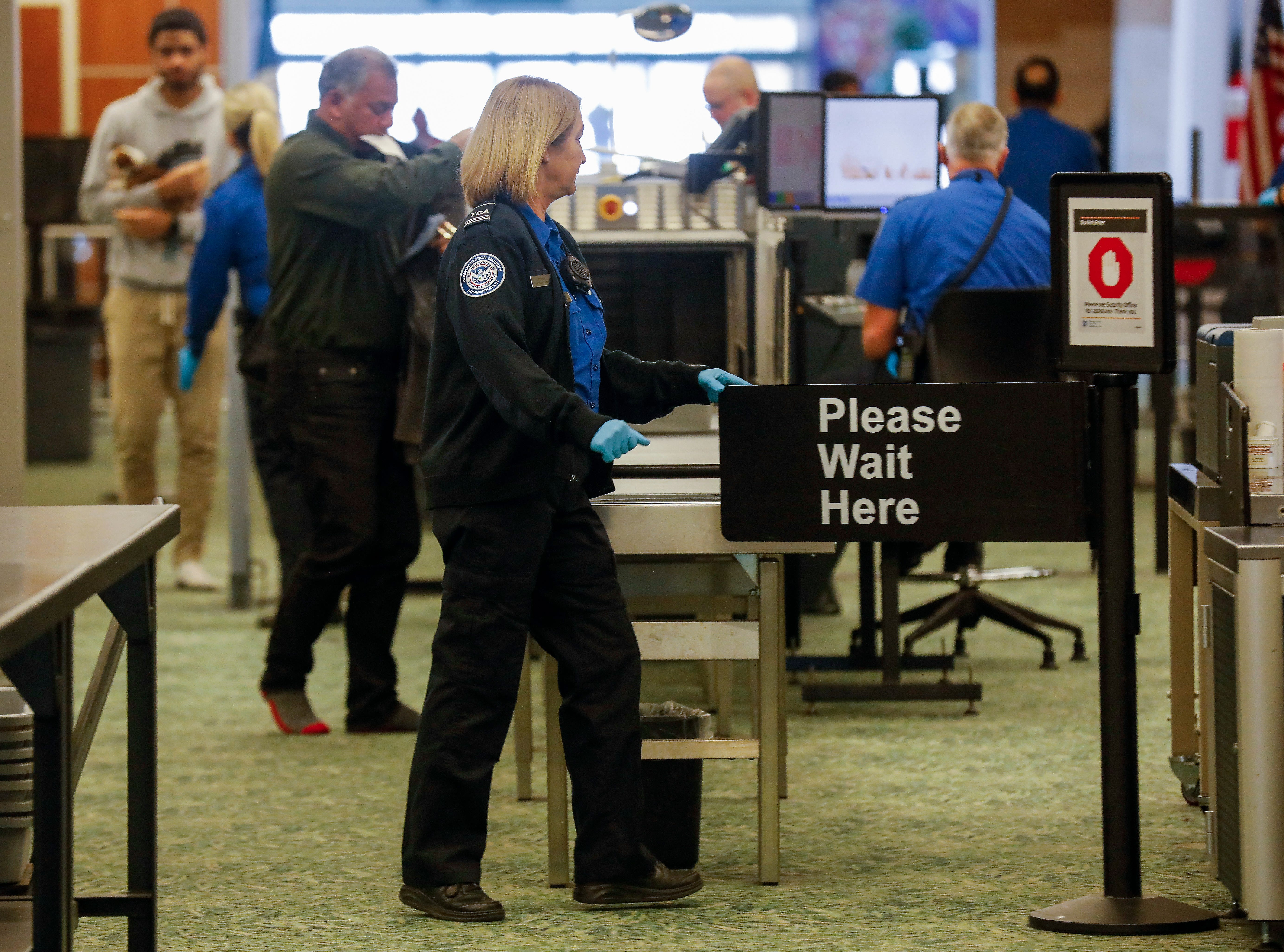 Transportation Security Administration employees screen passengers at the Springfield-Branson National Airport on Thursday, Jan. 10, 2019.