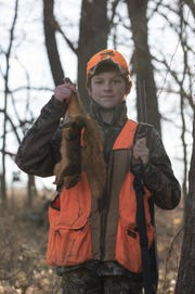 A young winter squirrel hunter with one of his squirrels.