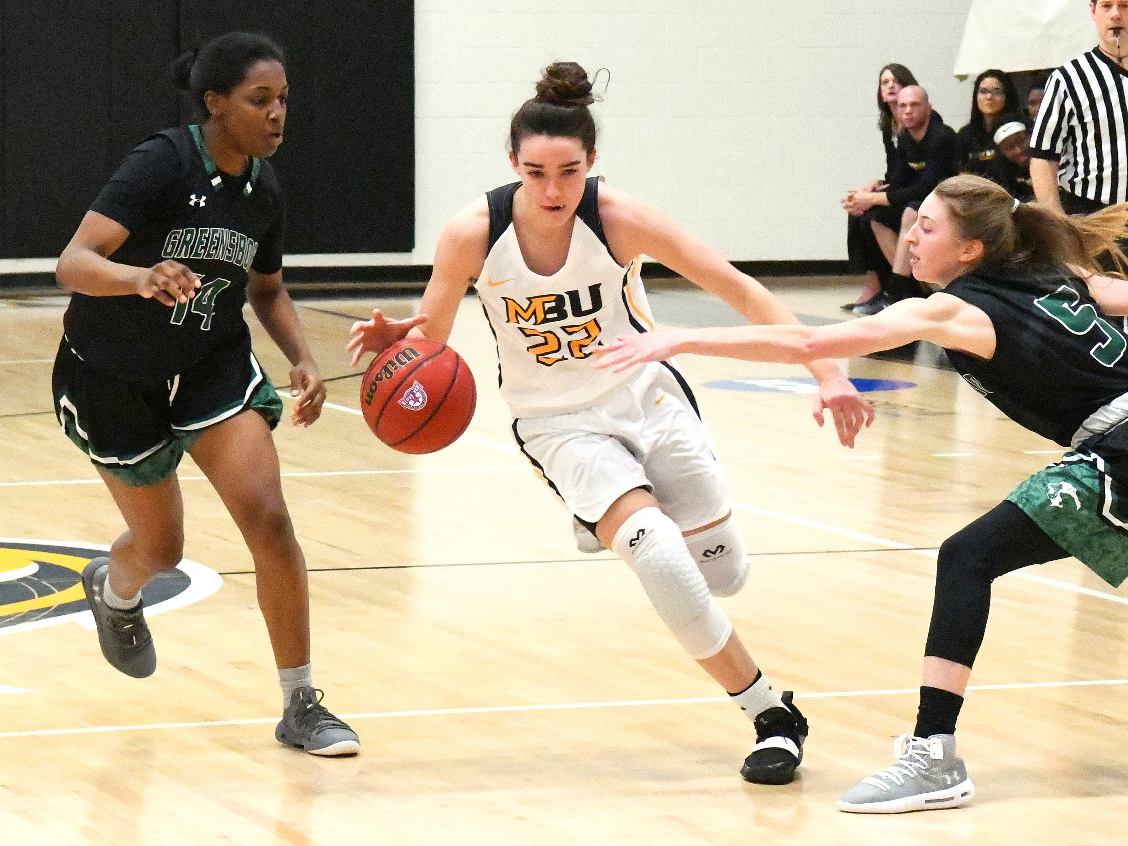 Mary Baldwin's Leah Calhoun takes the ball between Greensboro's Sabria Joseph (#14) and Katie Lewis (#5) during a USA South conference game played in Staunton on Jan. 9, 2019.
