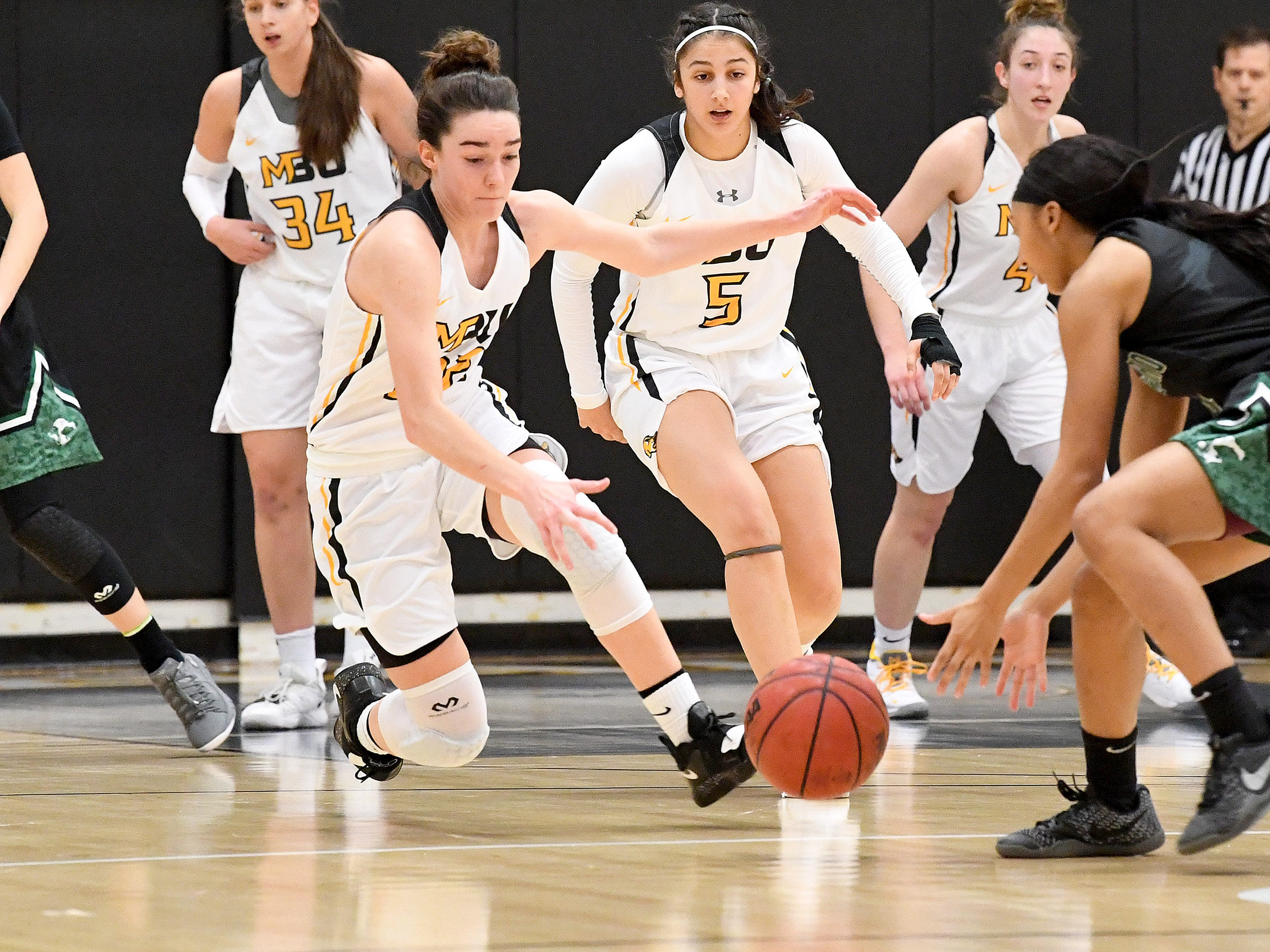 Mary Baldwin's Leah Calhoun (#22) begins to slide down to capture a loose ball with teammate Demet Saygili (#5) just behind her during a USA South conference game played in Staunton on Jan. 9, 2019.