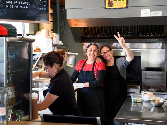 Co-owner Gloria Gerber (center) and prep cook Mery Reseresbo both look to the camera and smile as Leyla Bahena, who helps out in the kitchen for the day, continues preparing a customer's order at the newly expanded Glora's Pupuseria in Staunton on Thursday, Jan. 10, 2019. Gloria co-owns the El Salvadorian restaurant with her husband, John Gerber.