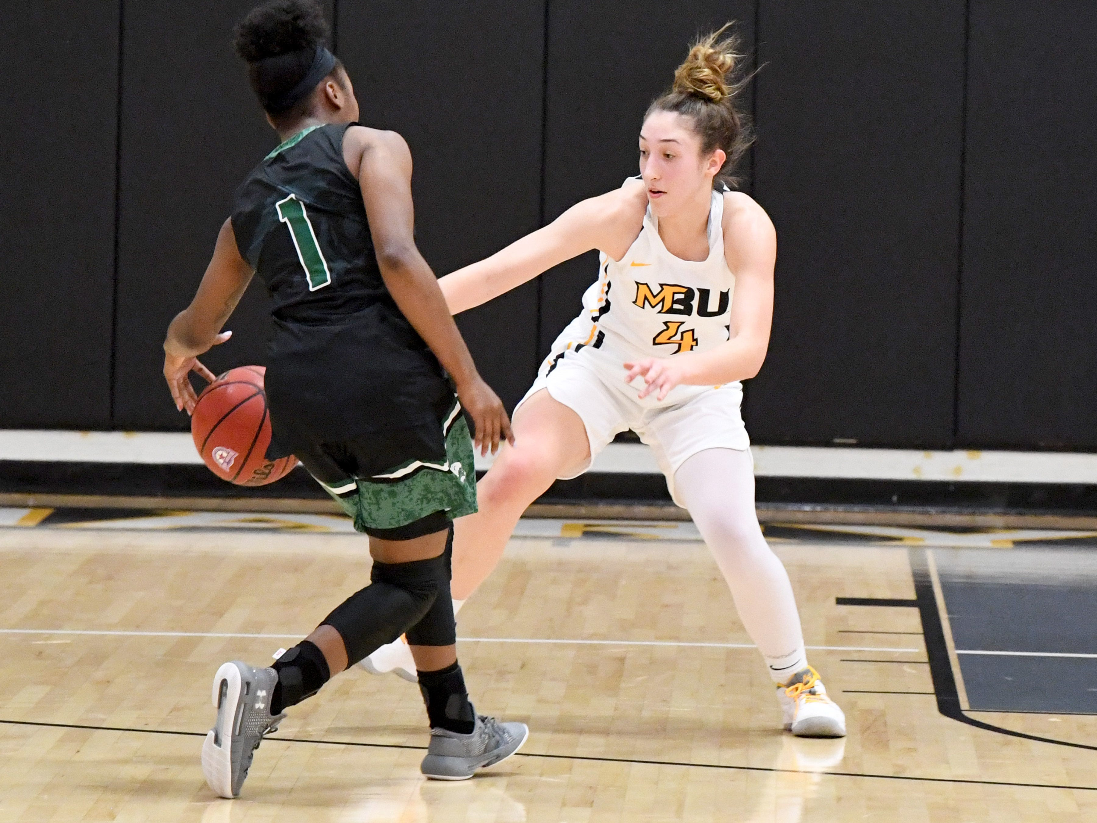 Mary Baldwin's Nicole Blackburn (#4) tries to strip the ball from Greensboro's Ashley Free during a USA South conference game played in Staunton on Jan. 9, 2019.