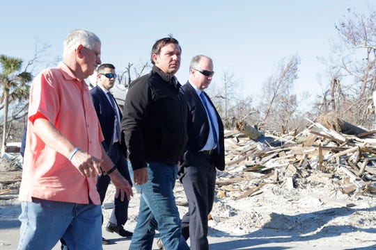 Mexico Beach Mayor Al Cathey, left, and Gov. Ron DeSantis, center, walk the streets of Mexico Beach, Wednesday, Jan. 9, 2019. Hurricane Michael left the panhandle in a total disarray on Oct. 10, 2018.
