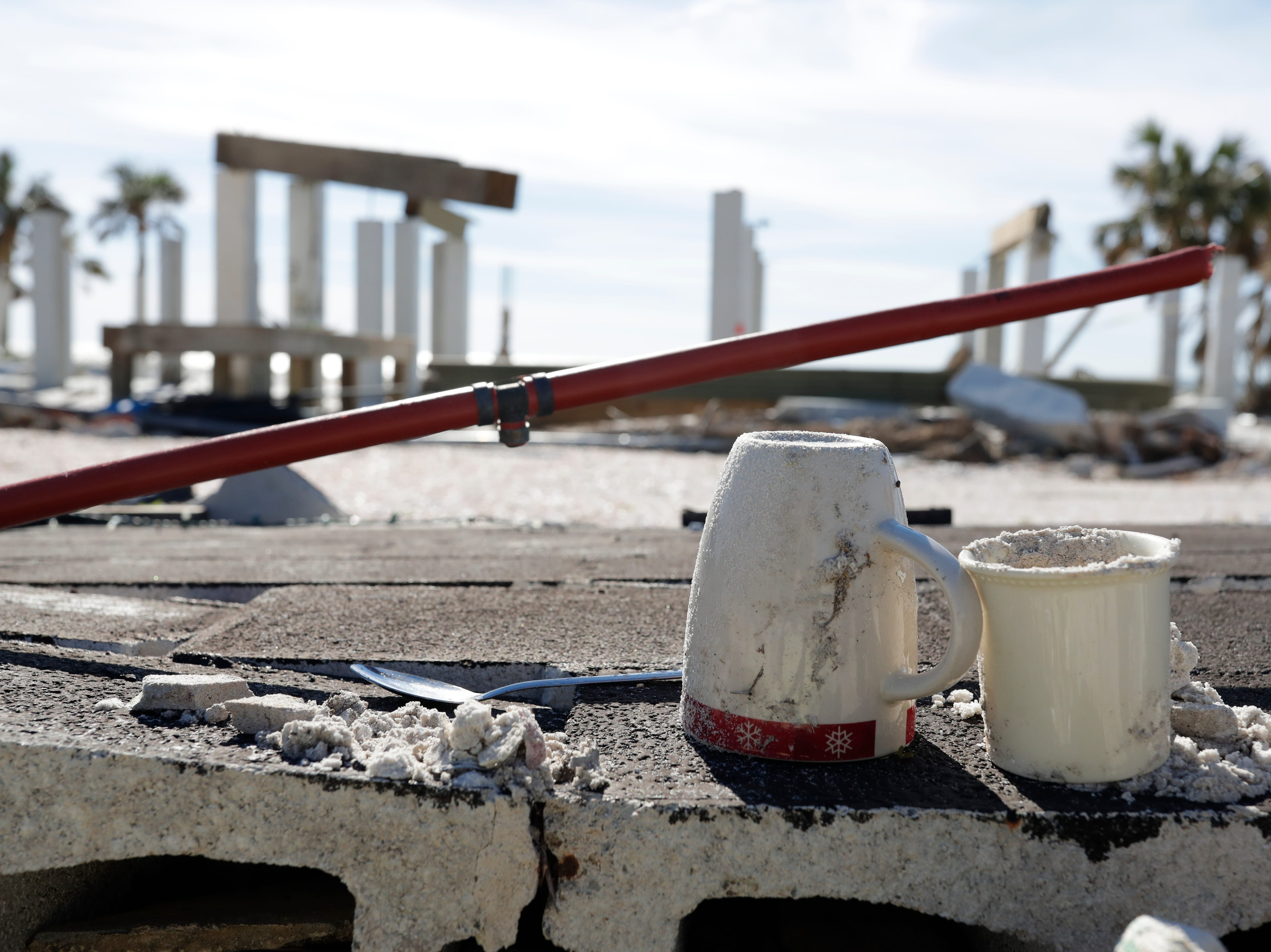 Two mugs and a spoon overlooking the ocean sit on a fallen wall in Mexico Beach, Wednesday, Jan. 9, 2019. Hurricane Michael left the panhandle in a total disarray on Oct. 10, 2018.