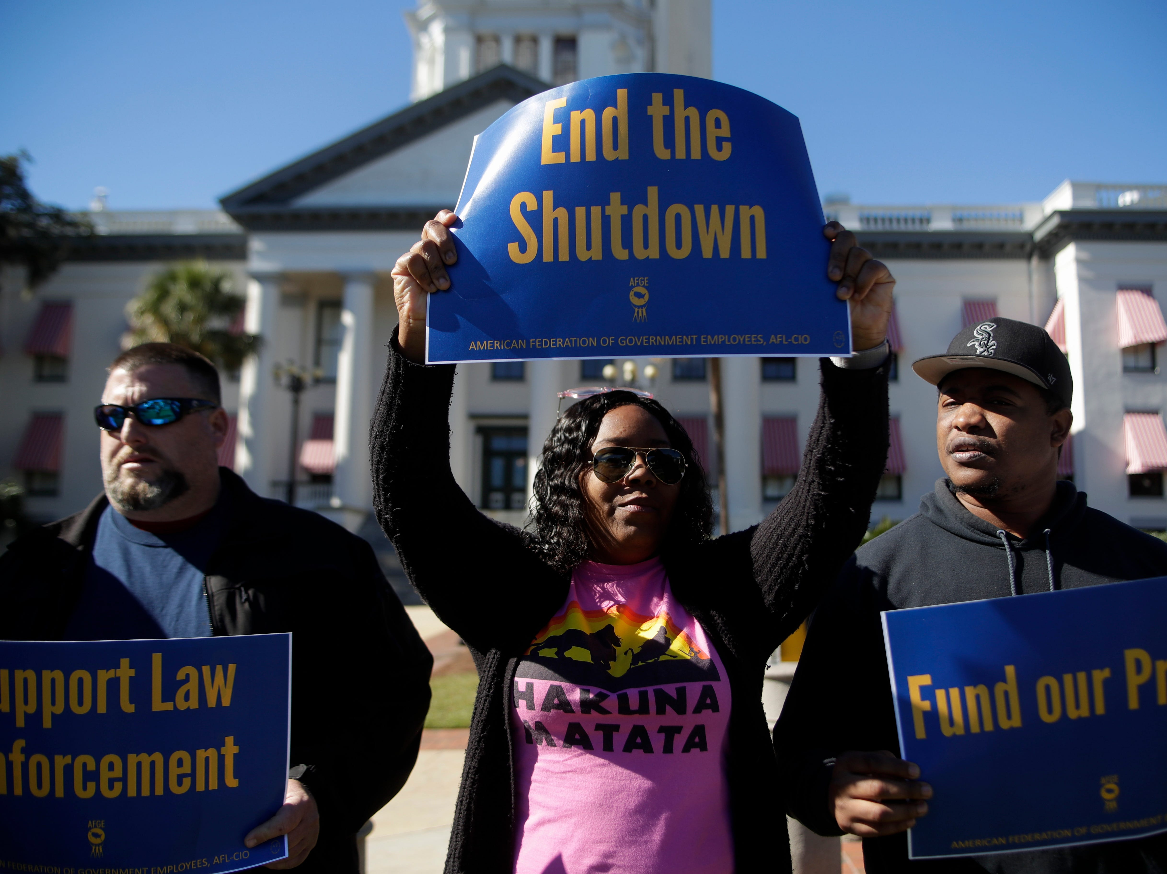 Casey Musgrove, left, Chandra Ward and Xavier Ward rally in front of the Florida Historic Capitol along with several dozen other federal employees in protest of the government shutdown that has left them without pay Thursday, Jan. 10, 2019.