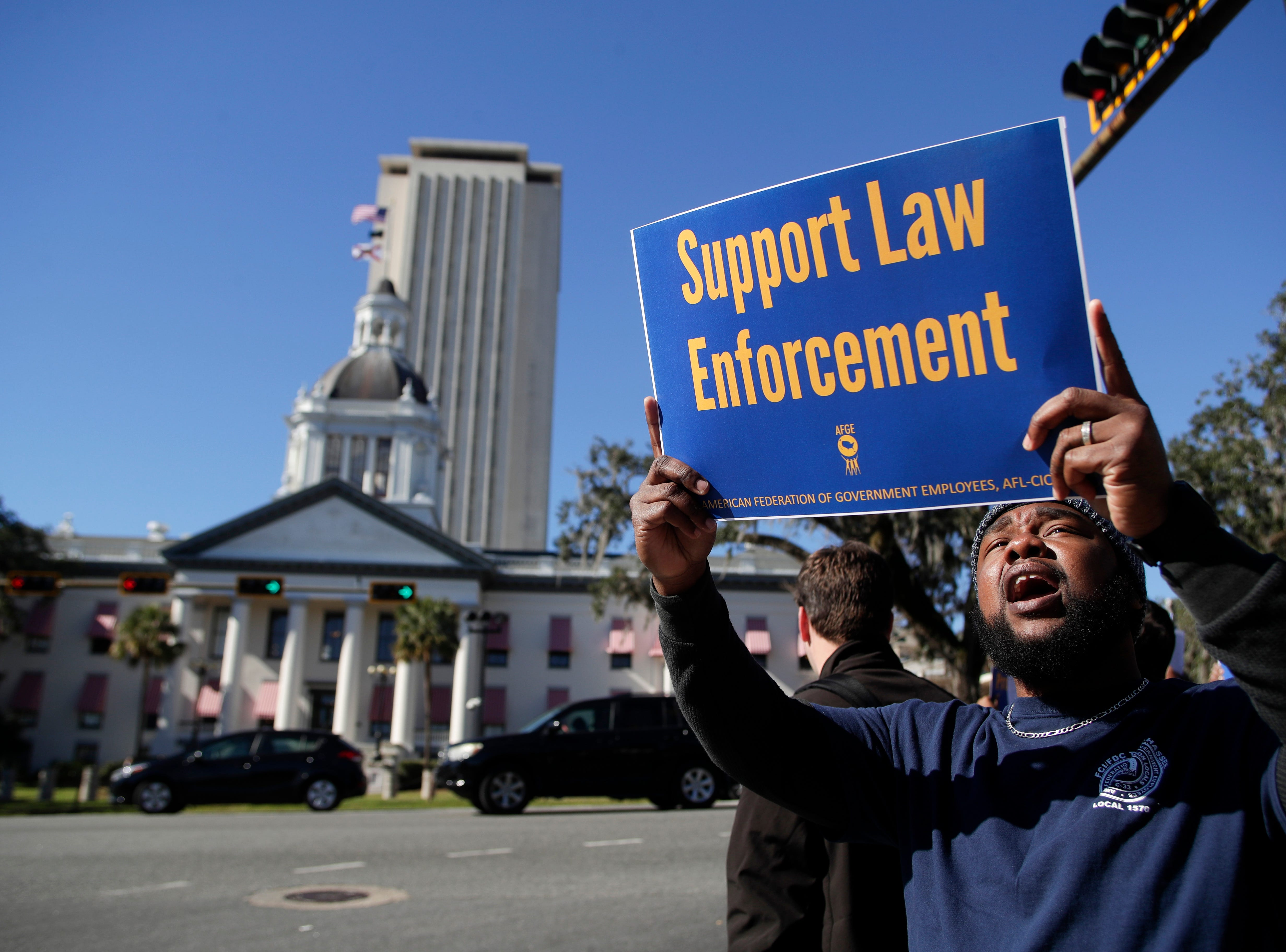 Federal Correctional Institution employee Alex Dudley protests from the corner of Apalachee Parkway and Monroe Street in front of the Florida Historic Capitol as he and other federal workers rallied against the government shutdown in downtown Tallahassee Thursday, Jan. 10, 2019.