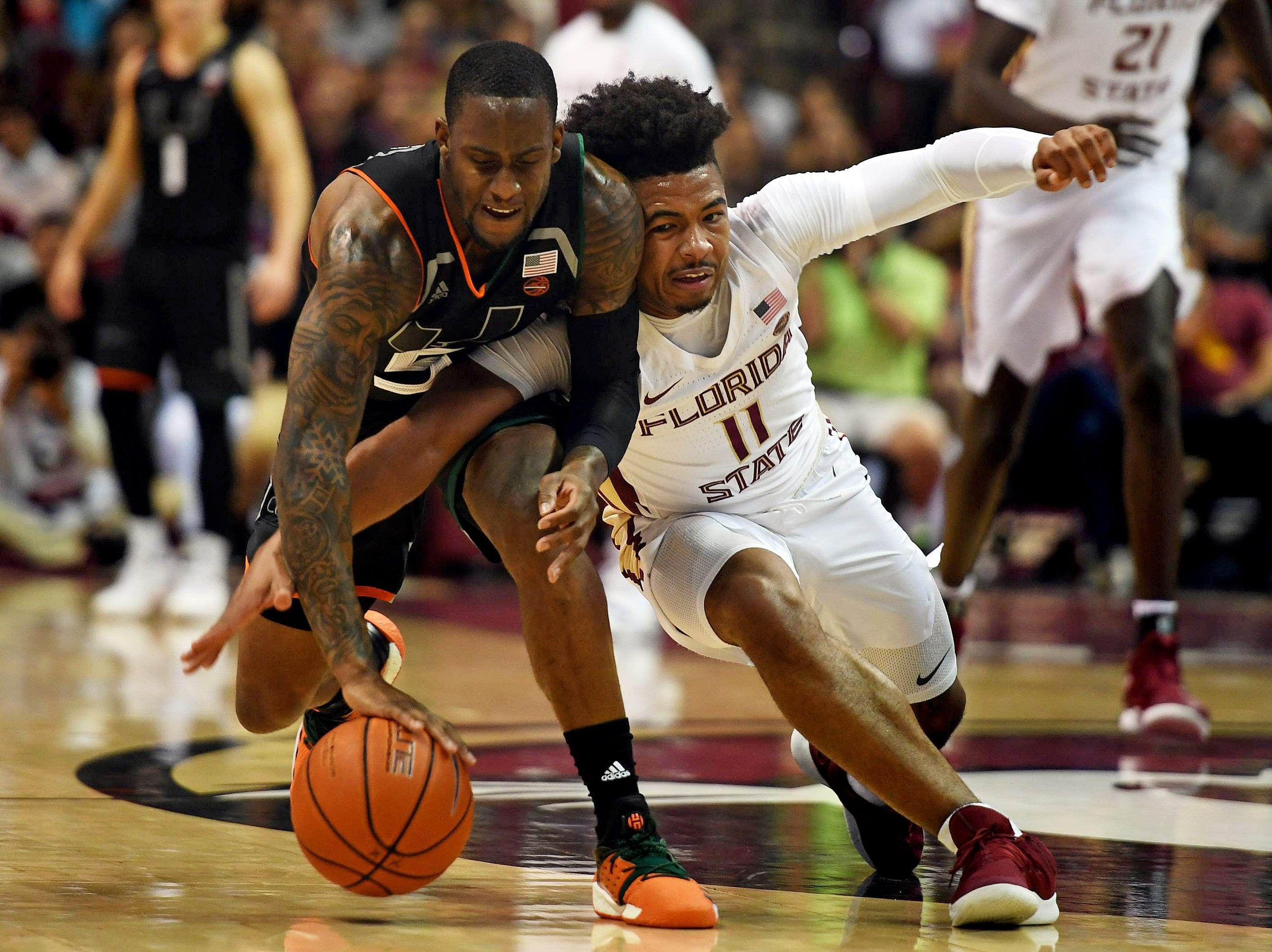 Jan 9, 2019; Tallahassee, FL, USA; Florida State Seminoles guard David Nichols (11) fights for a loose ball against Miami Hurricanes guard Zach Johnson (5) during the first half at Donald L. Tucker Center. Mandatory Credit: Melina Myers-USA TODAY Sports