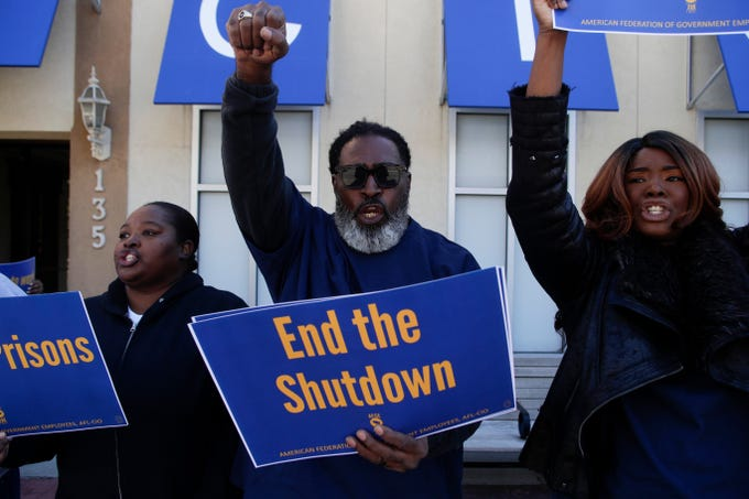 Latoya Gainous, left, Rich Johnson and Temeka Hunter-Johnson, all Federal Correctional Institution workers, chant together in front of the Federation of Labor and Congress of Industrial Organizations (AFL-CIO) building in Tallahassee before marching to the Florida Historic Capitol in protest of the government shutdown Thursday, Jan. 10, 2019. Johnson and Hunter-Johnson are married and are both without pay through the shutdown.