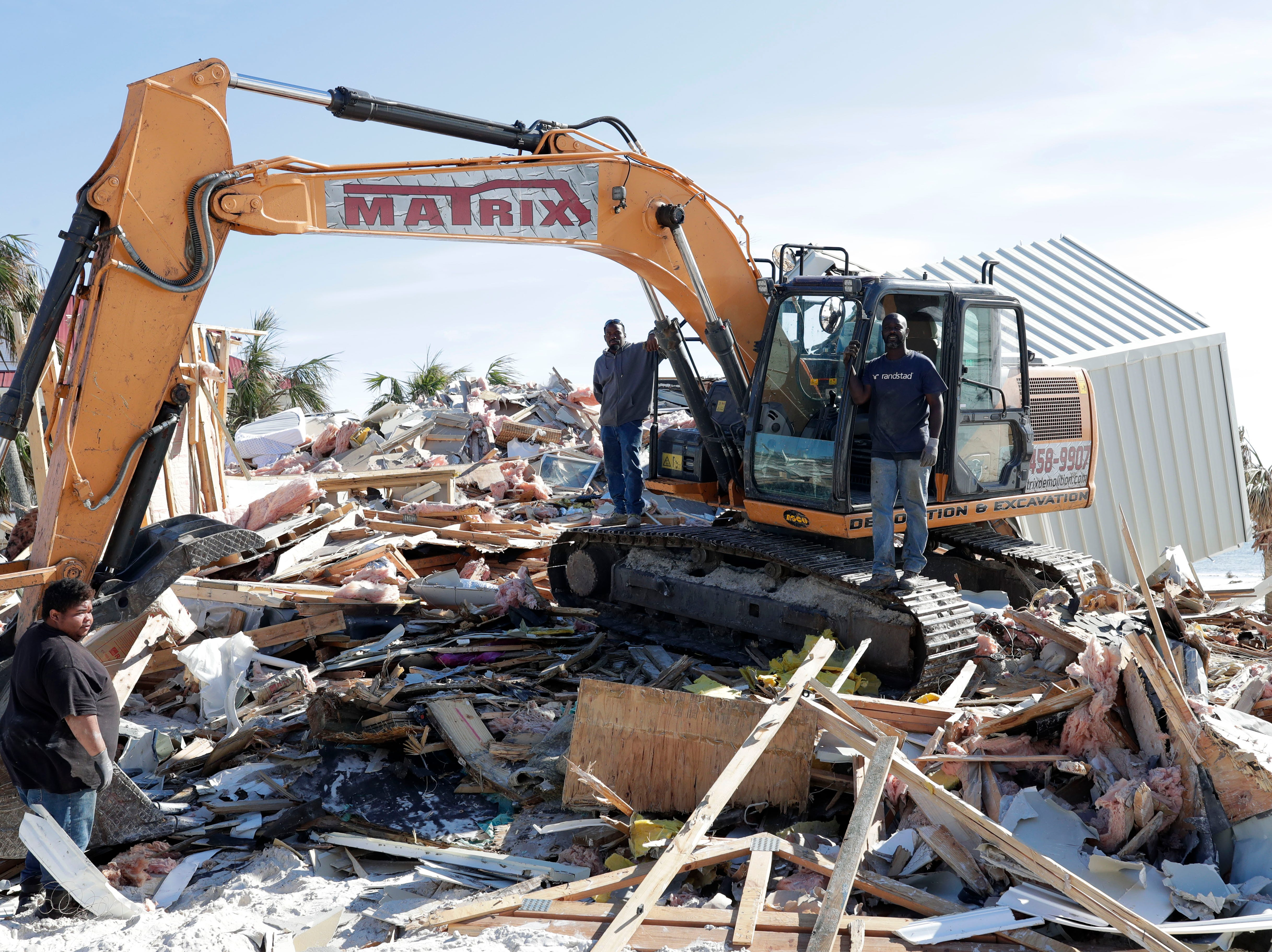 Reggie Twons, left, Ricky Bobby, and Derek Lee, who work for a demolition company stand with a demolition machine which sits on top of what was once a beachfront home in Mexico Beach, Wednesday, Jan. 9, 2019. Hurricane Michael left the panhandle in a total disarray on Oct. 10, 2018.