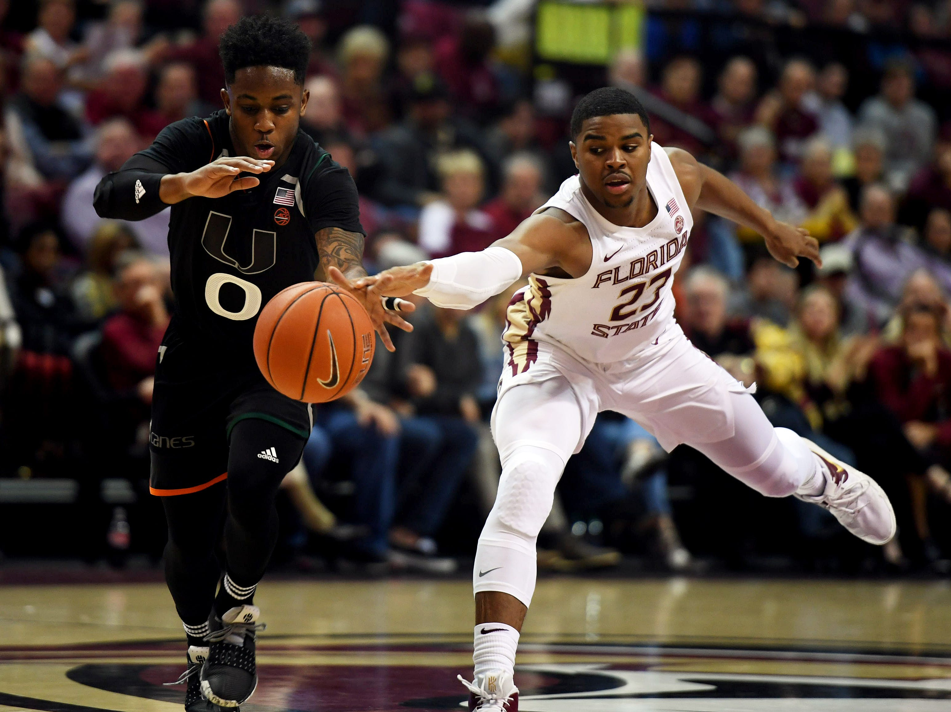 Jan 9, 2019; Tallahassee, FL, USA; Miami Hurricanes guard Chris Lykes (0) fights for a loose ball against Florida State Seminoles guard MJ Walker (23) during the first half at Donald L. Tucker Center. Mandatory Credit: Melina Myers-USA TODAY Sports
