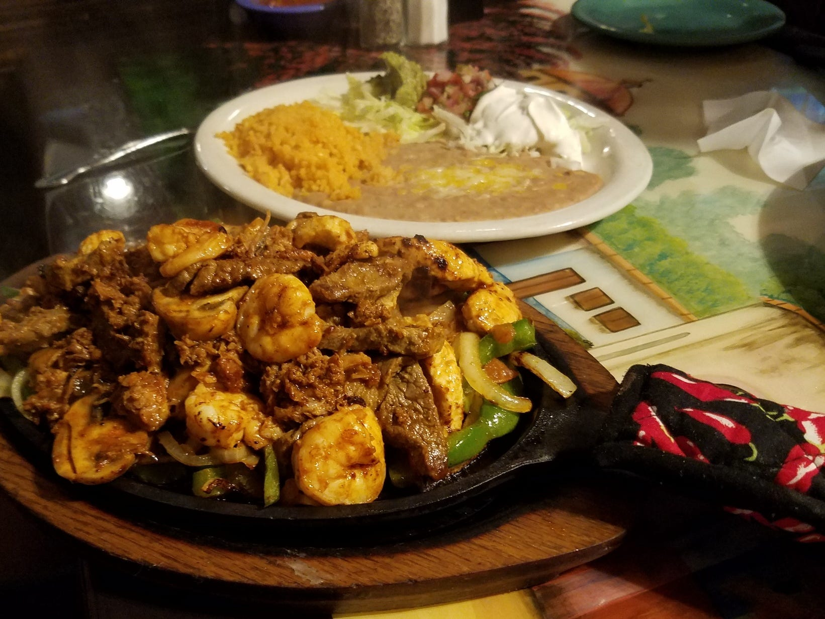 The fajita parrilladas combines five different meats with sauteed vegetables and is served with all the trimmings.