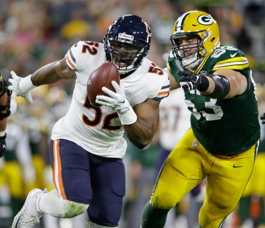 In this Sunday, Sept. 9, 2018, file photo, Chicago Bears' Khalil Mack (52) intercepts a pass and returns it for a touchdown as Green Bay Packers' Corey Linsley (63) gives chase during the first half of an NFL football game in Green Bay, Wisconsin.