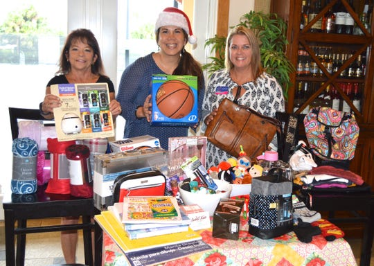Vero Beach Christian Business Association Secretary Debbie Fields and board member Brenda Sposato present Angel Pietsch of Little Birthday Angels with teen gifts donated by association members.