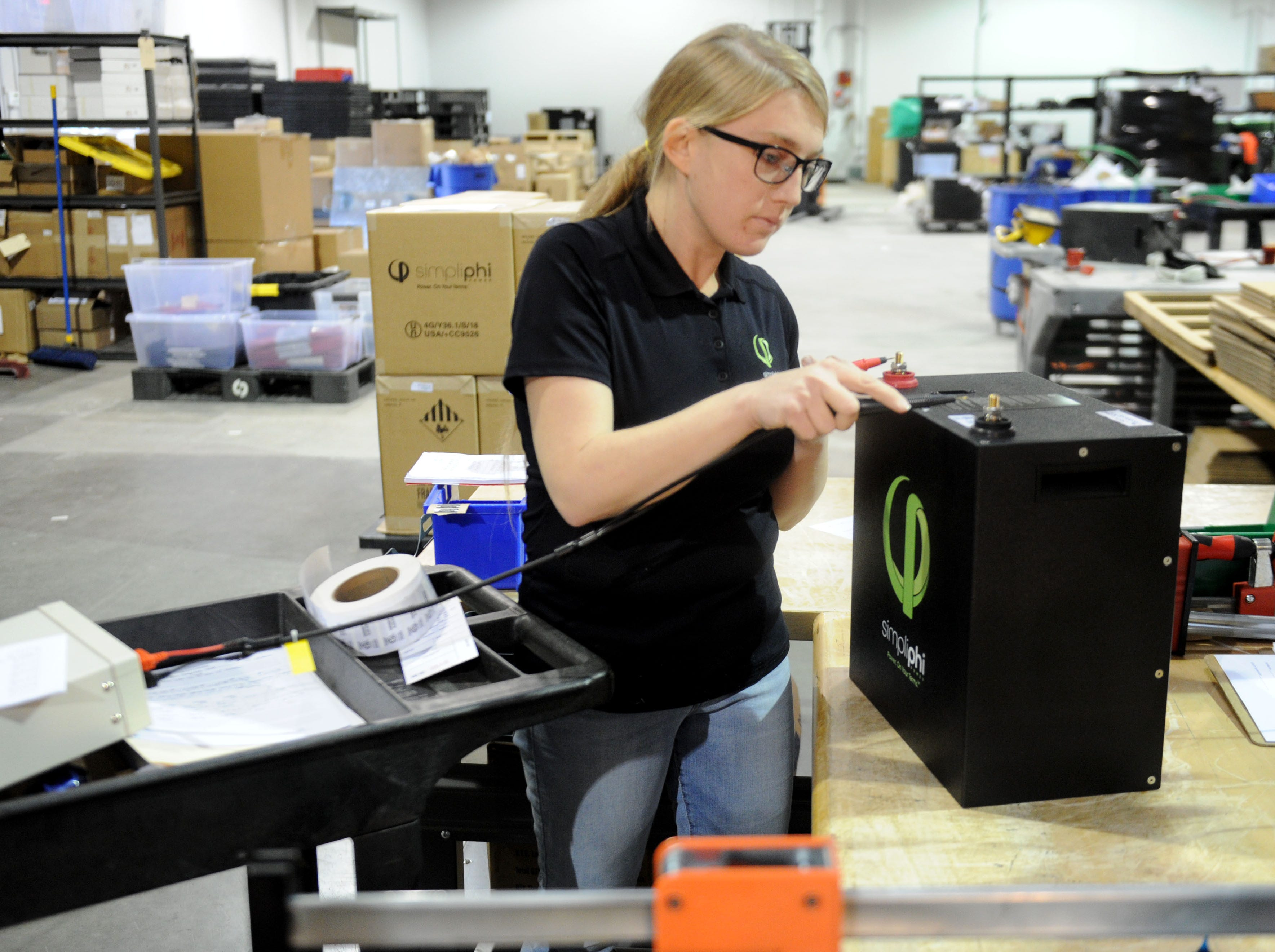 Cindy Bowhall, a manufacturing technician for SimpliPhi Power, checks the power on one of the batteries in the company's new manufacturing facility in Oxnard. The company's batteries are aimed at areas off the normal power grid or for use if the power grid fails.