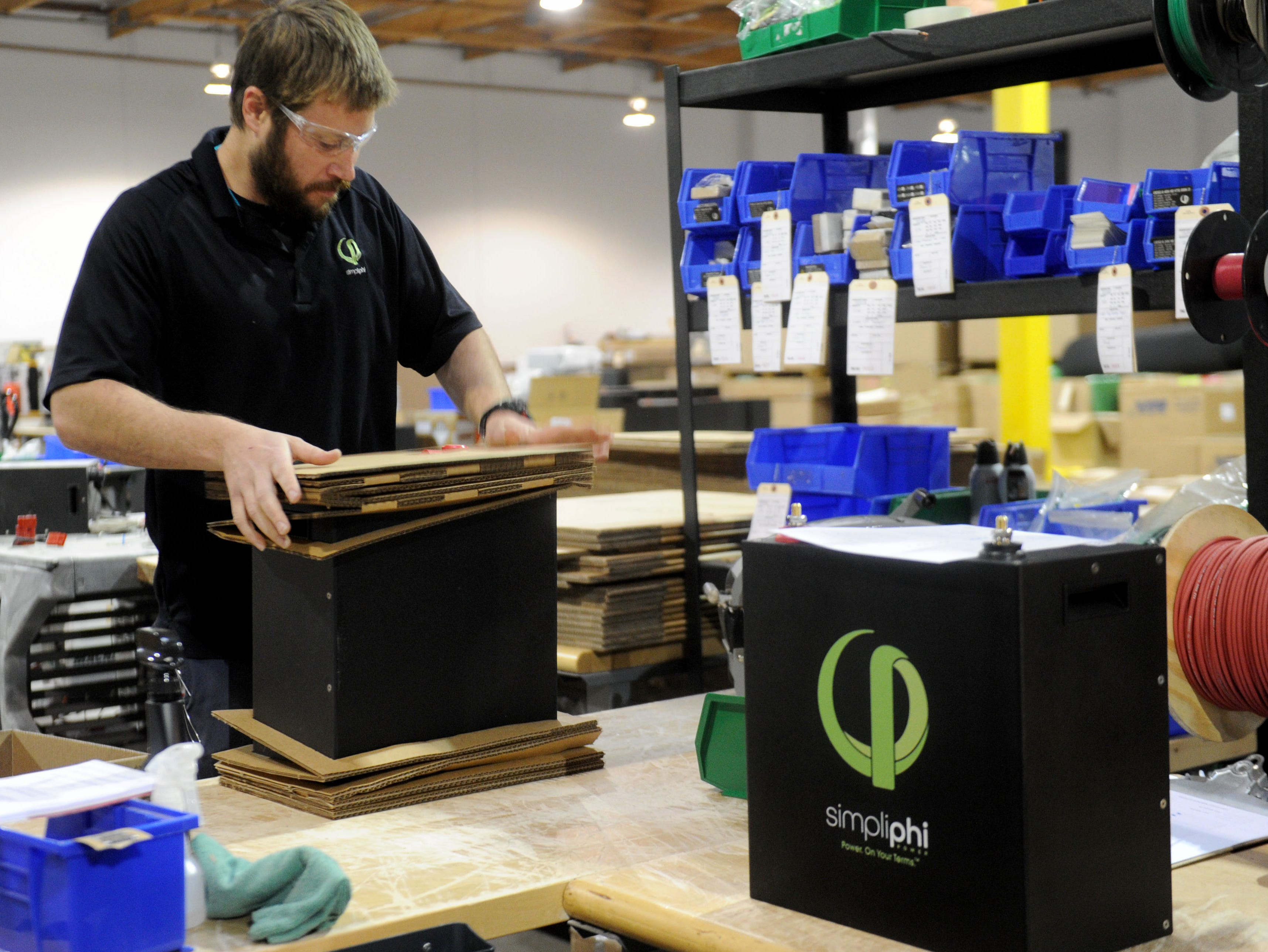Austin Childs, a shipping and receiving specialist for SimpliPhi Power, works on boxing a battery in the company's new manufacturing facility in Oxnard. The new facility is triple the size of its previous Ojai headquarters. The company aims to expand its international operations and the Oxnard facility is crucial to that.