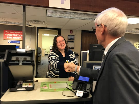 Gov. Tony Evers shakes hands with a Wausau DMV employee Thursday.