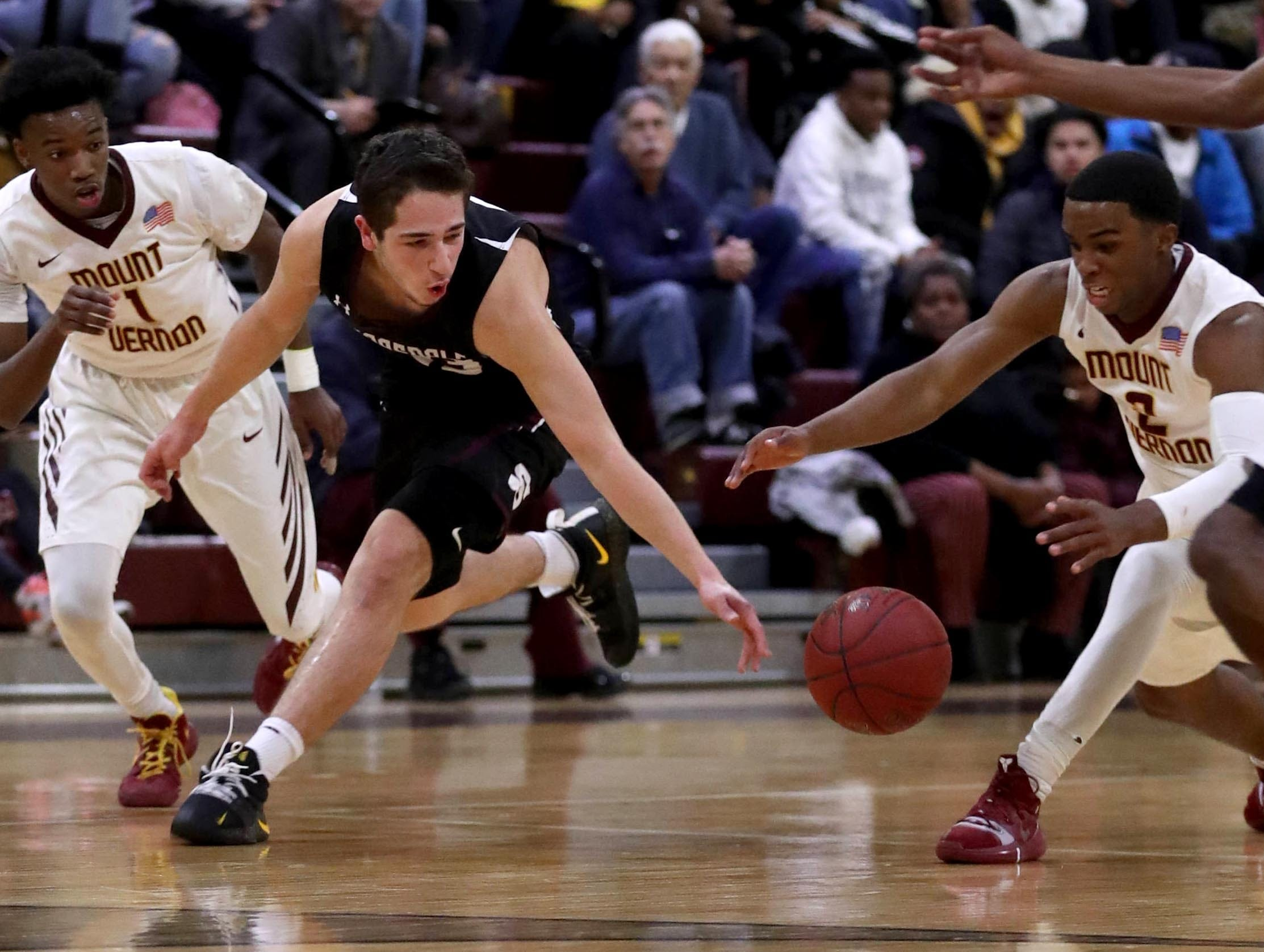 Cole Kattan of Scarsdale and Joel Cooper of Mount Vernon chase a loose ball during a varsity basketball game at Mount Vernon High School Jan. 9, 2019. Mount Vernon defeated Scarsdale 70-54.