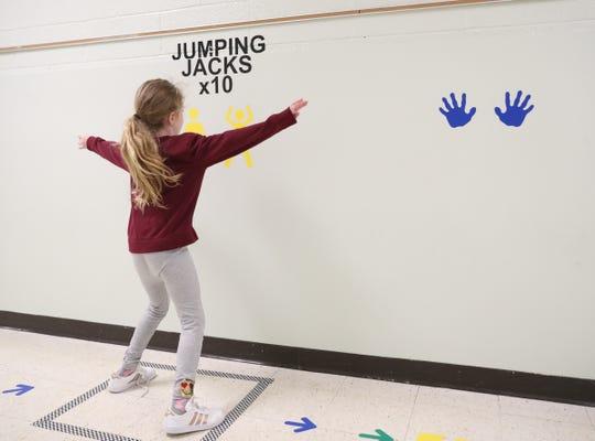 Second grader Leia Egan does jumping jacks along the sensory path in the hallway at Sloatsburg Elementary School in Sloatsburg on Thursday, January 10, 2019.