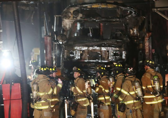 Yorktown firefighters work in front of a destroyed school bus at the scene of a 2-alarm fire in the Baumann Bus Garage on Front Street in Yorktown Jan. 9, 2019.