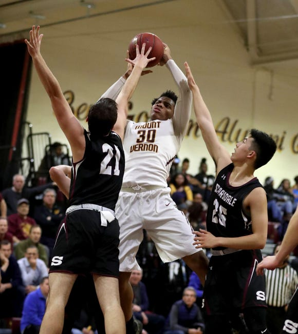 Troy Hupstead of Mount Vernon shoots between Samuel Thompson and Evan Huo of Scarsdale during a varsity basketball game at Mount Vernon High School Jan. 9, 2019. Mount Vernon defeated Scarsdale 70-54.