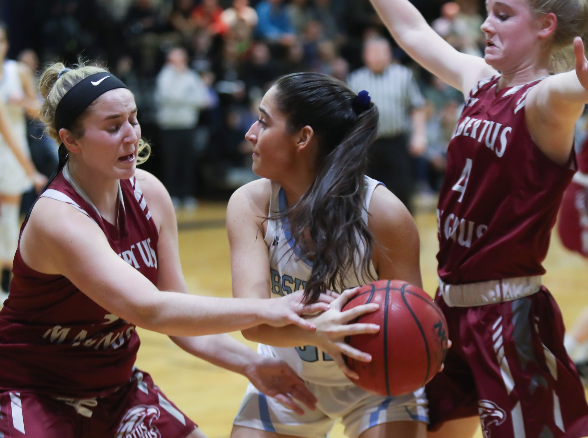 Ursuline's Carolina Brennan (21) is boxed in by Albertus' Chloe Cavallo (34) and Sierra Linnin (4) during girls varsity basketball action at The Ursuline School in New Rochelle on Wednesday, January 9, 2019.  Ursuline defeated Albertus 68-48.