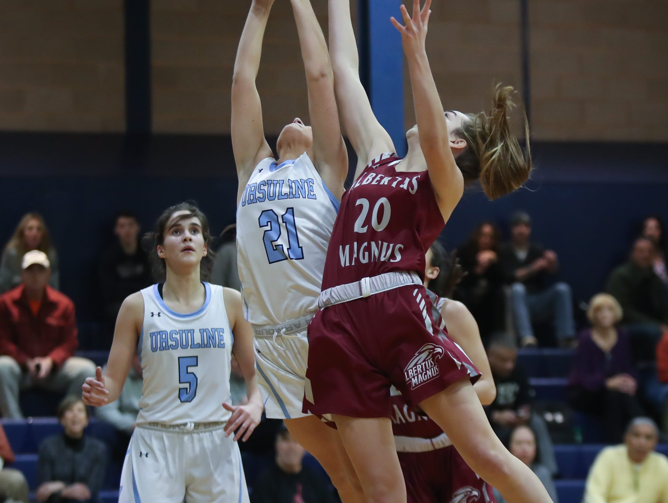 Ursuline's Carloine Brennan (21) and Albertus' Sam Bischoff (20) work to pull in a rebound during girls varsity basketball action at The Ursuline School in New Rochelle on Wednesday, January 9, 2019.  Ursuline defeated Albertus 68-48.