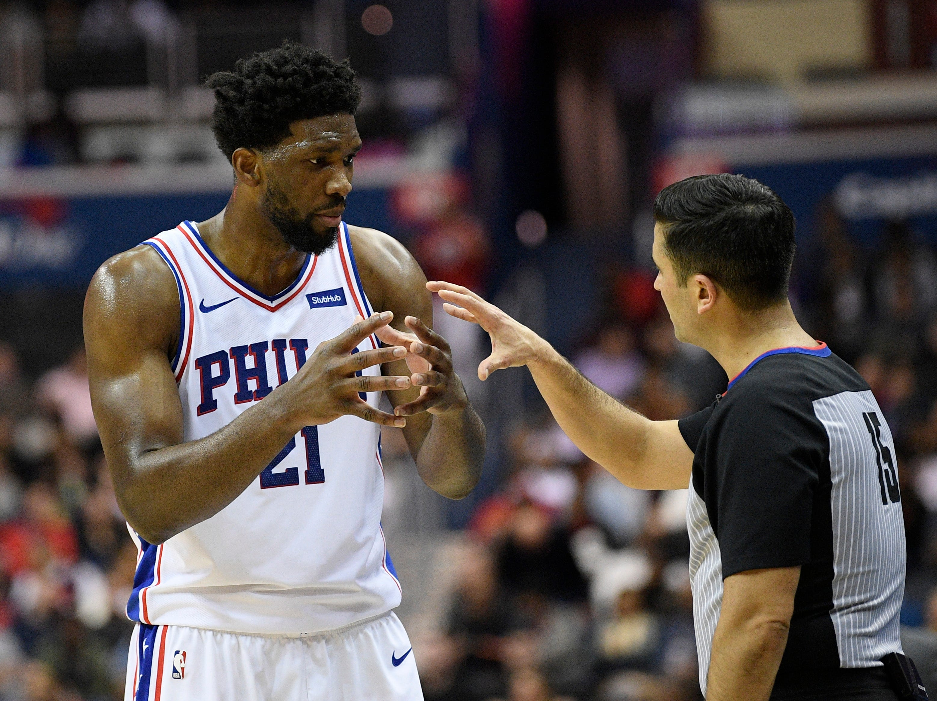 Philadelphia 76ers center Joel Embiid (21) talks with referee Zach Zarba (15) during the first half of an NBA basketball game against the Washington Wizards, Wednesday, Jan. 9, 2019, in Washington. (AP Photo/Nick Wass)