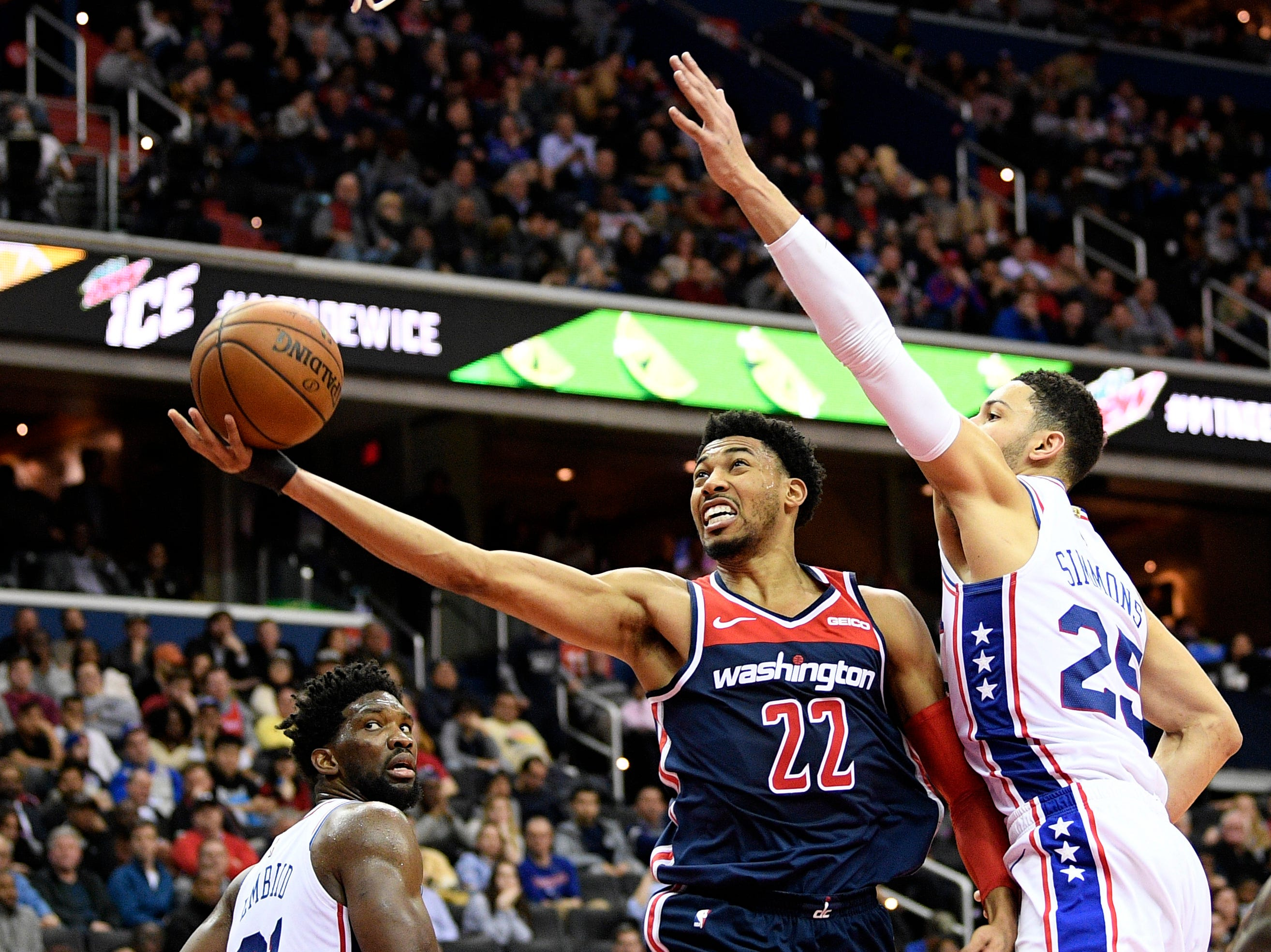 Washington Wizards forward Otto Porter Jr. (22) goes to the basket against Philadelphia 76ers guard Ben Simmons (25) and center Joel Embiid, left, during the second half of an NBA basketball game, Wednesday, Jan. 9, 2019, in Washington. The Wizards won 123-106. (AP Photo/Nick Wass)