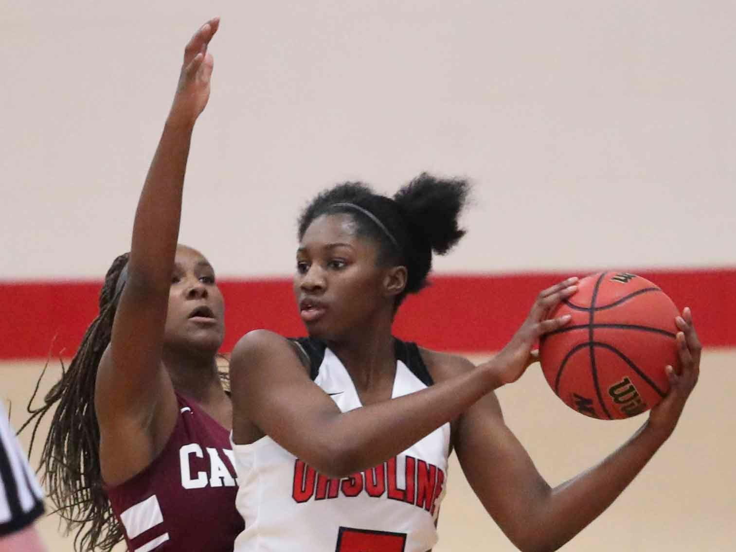 Ursuline's Kayounor Wulah (5) keeps the ball away from Caravel's Sasha Marvel in the Bucs' 42-31 win at Ursuline Wednesday.
