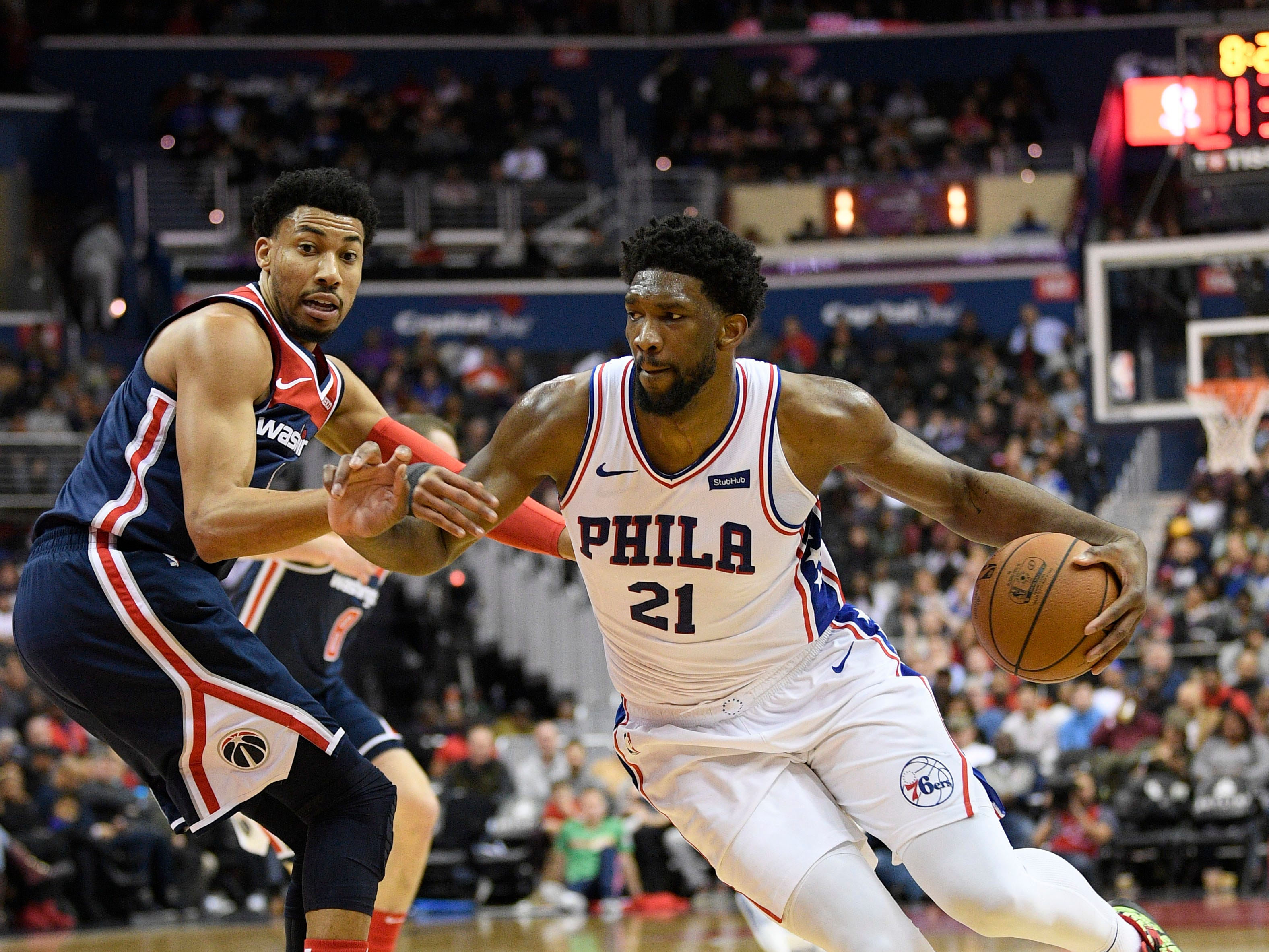 Philadelphia 76ers center Joel Embiid (21) dribbles the ball against Washington Wizards forward Otto Porter Jr., left, during the first half of an NBA basketball game, Wednesday, Jan. 9, 2019, in Washington. (AP Photo/Nick Wass)