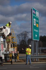 Crews reveal signs for the newly opened U.S 301 toll road near Middletown Thursday.