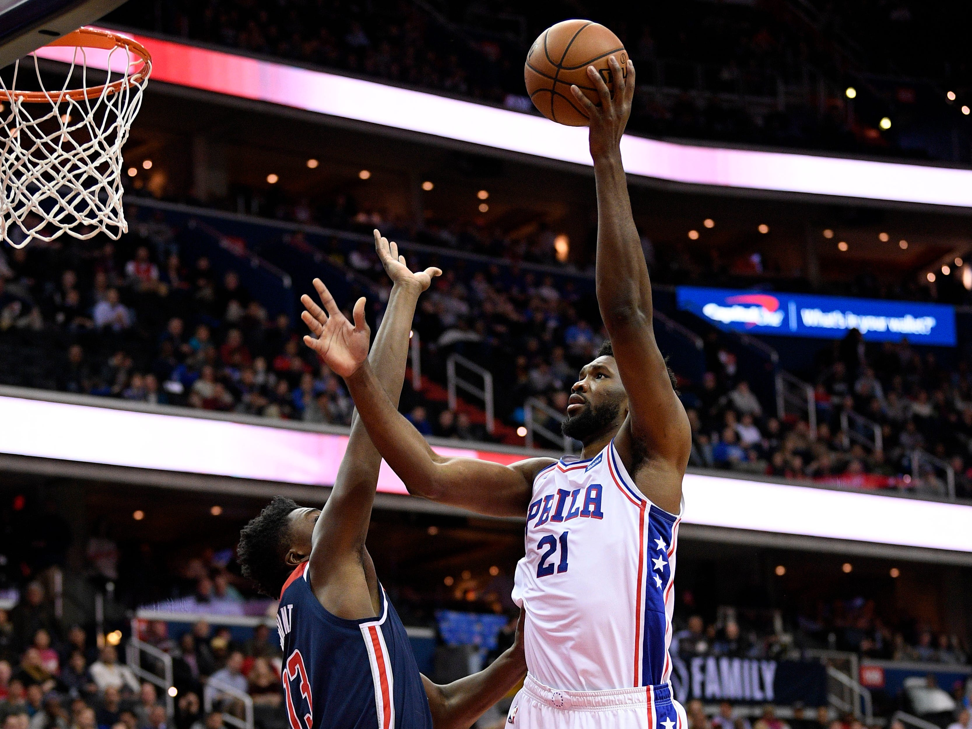 Philadelphia 76ers center Joel Embiid (21) goes to the basket against Washington Wizards center Thomas Bryant (13) during the first half of an NBA basketball game, Wednesday, Jan. 9, 2019, in Washington. (AP Photo/Nick Wass)