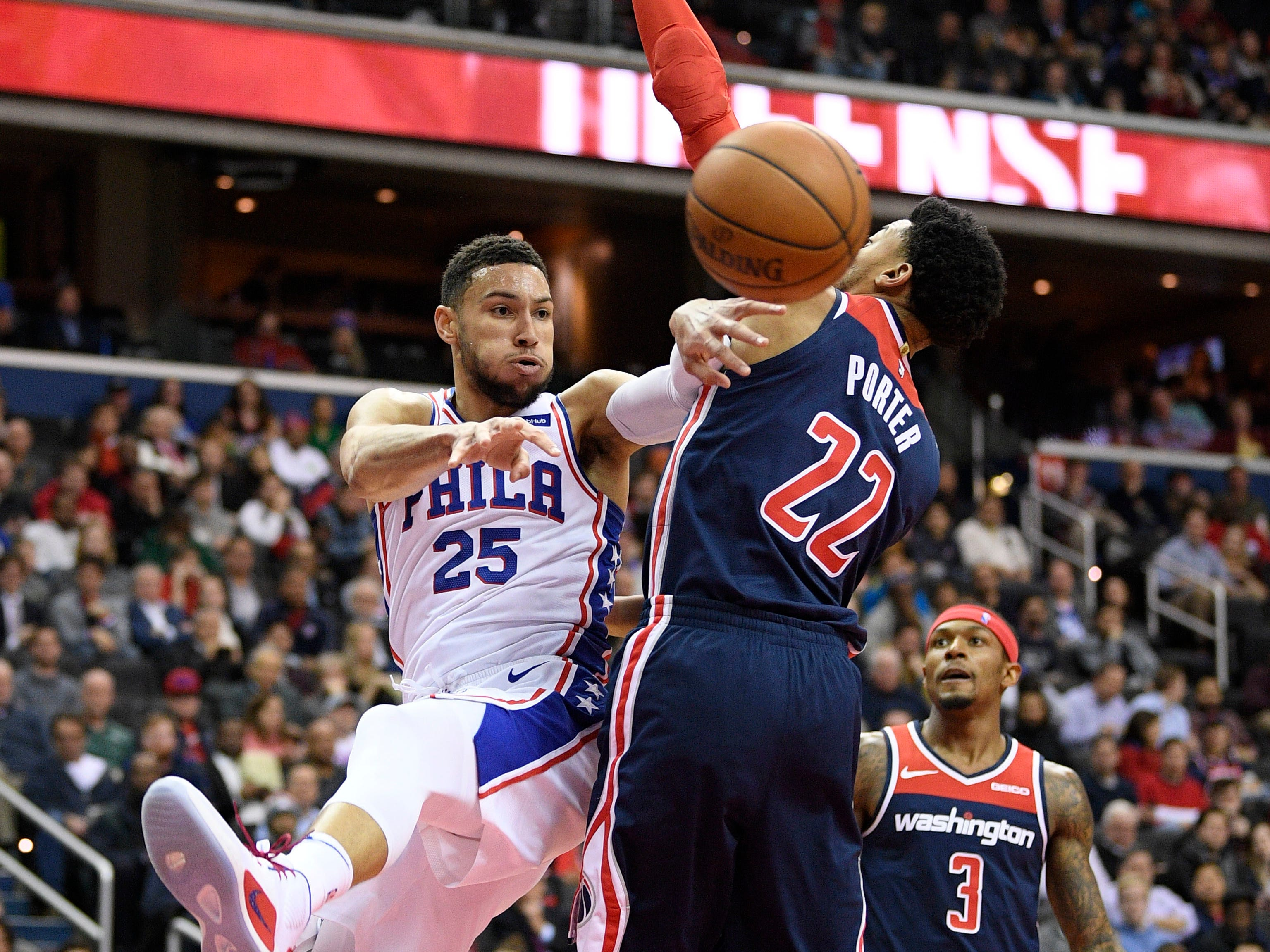 Philadelphia 76ers guard Ben Simmons (25) passes the ball against Washington Wizards forward Otto Porter Jr. (22) and guard Bradley Beal (3) during the first half of an NBA basketball game, Wednesday, Jan. 9, 2019, in Washington. (AP Photo/Nick Wass)