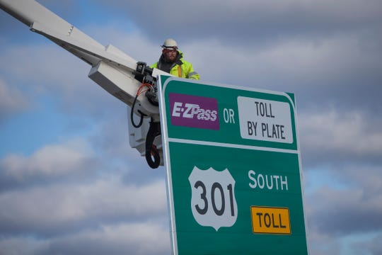 Crews reveal signs for the newly opened U.S. 301 mainline toll road near Middletown Thursday.