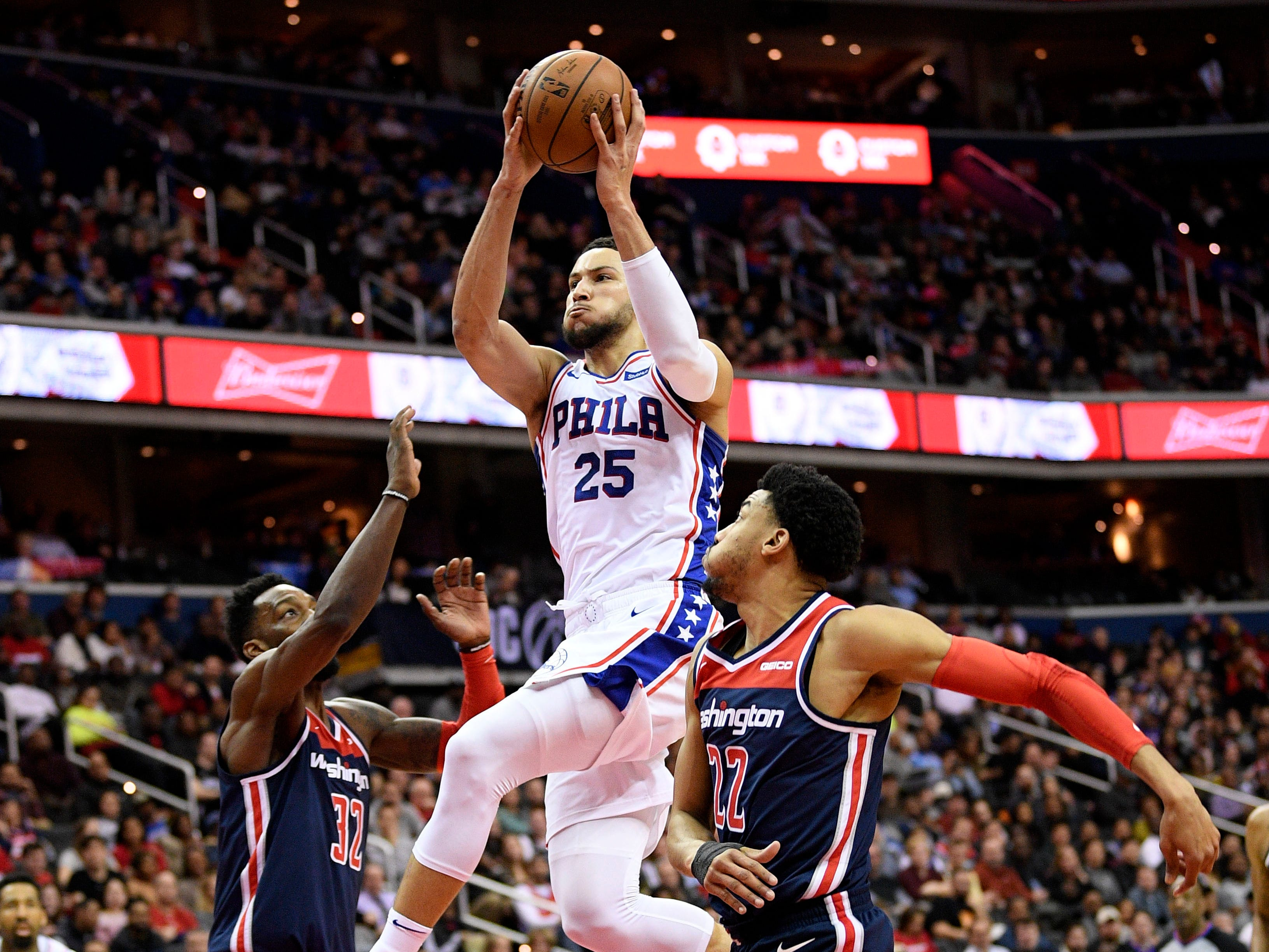 Philadelphia 76ers guard Ben Simmons (25) goes to the basket against Washington Wizards forward Otto Porter Jr. (22) and forward Jeff Green (32) during the first half of an NBA basketball game, Wednesday, Jan. 9, 2019, in Washington. (AP Photo/Nick Wass)