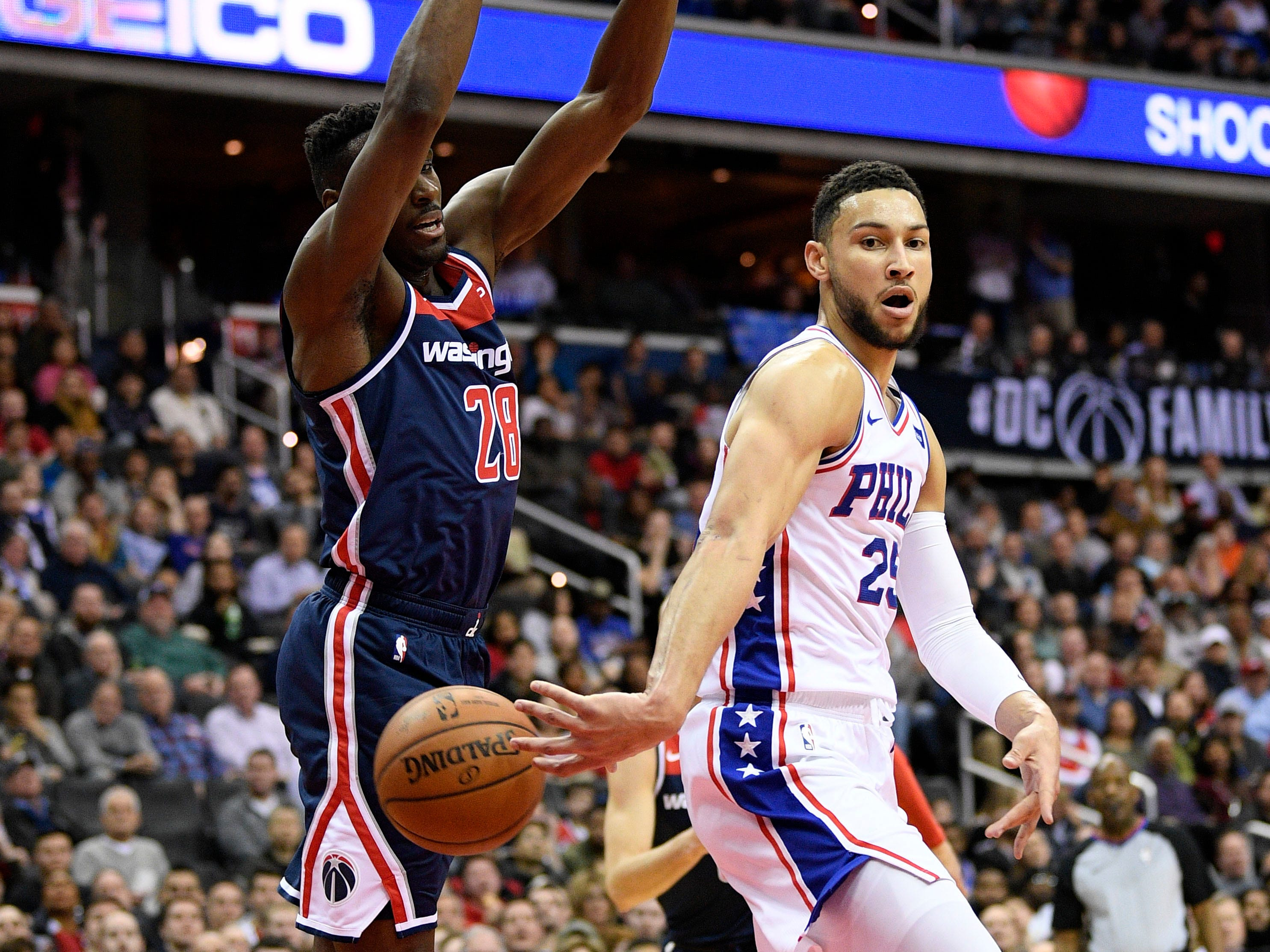 Philadelphia 76ers guard Ben Simmons (25) passes the ball behind the back against Washington Wizards center Ian Mahinmi (28) during the first half of an NBA basketball game, Wednesday, Jan. 9, 2019, in Washington. (AP Photo/Nick Wass)