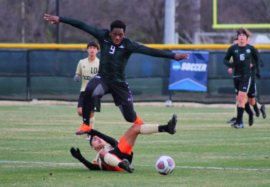 Rider's Trance Saenz makes a slide tackle against Lake Ridge's Etienne Taffou in the boys tournament at MSU Stang Park Thursday afternoon.