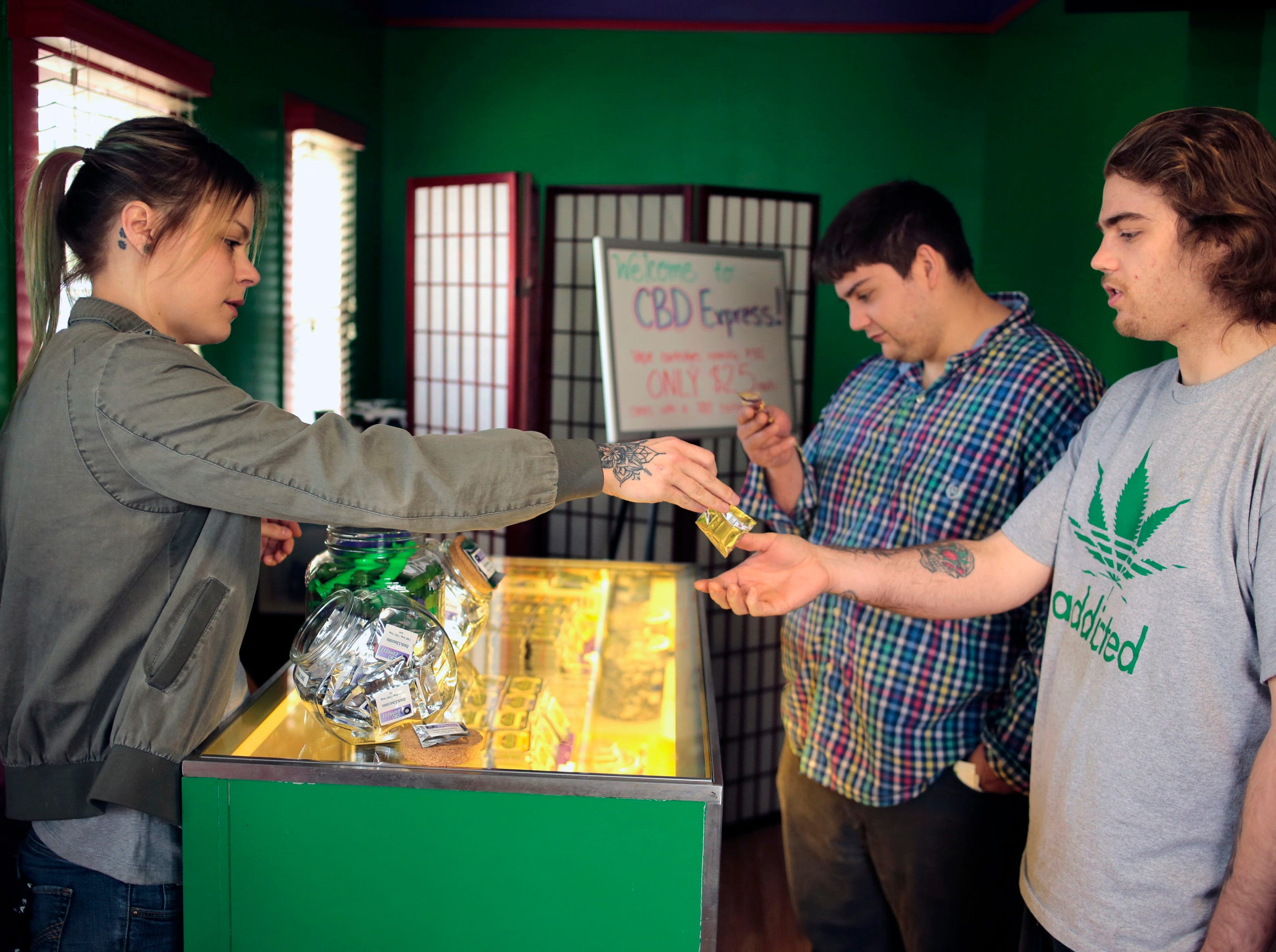 Jordin Hoefler, left, hands out a free dark chocolate edible to Tyler Rhodes, center, and Spencer Rhodes, right, during the CBD Express grand opening in Salem, Ore on  April 20, 2018 photo. The business sells CBD oils and CBD products. Applications for state licenses to grow hemp, marijuana's non-intoxicating cousin, have increased more than twentyfold since 2015 and Oregon now ranks No. 2 behind Colorado among the 19 states with hemp cultivation.