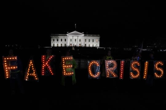 "Activists hold a lit ""FAKE CRISIS"" sign as they stage a protest outside the White House in response to U.S. President Donald Trumps prime time address to the nation Jan. 8, 2019 in Washington, DC. President Trump urged Congress to fund $5.7 billion for a border wall."