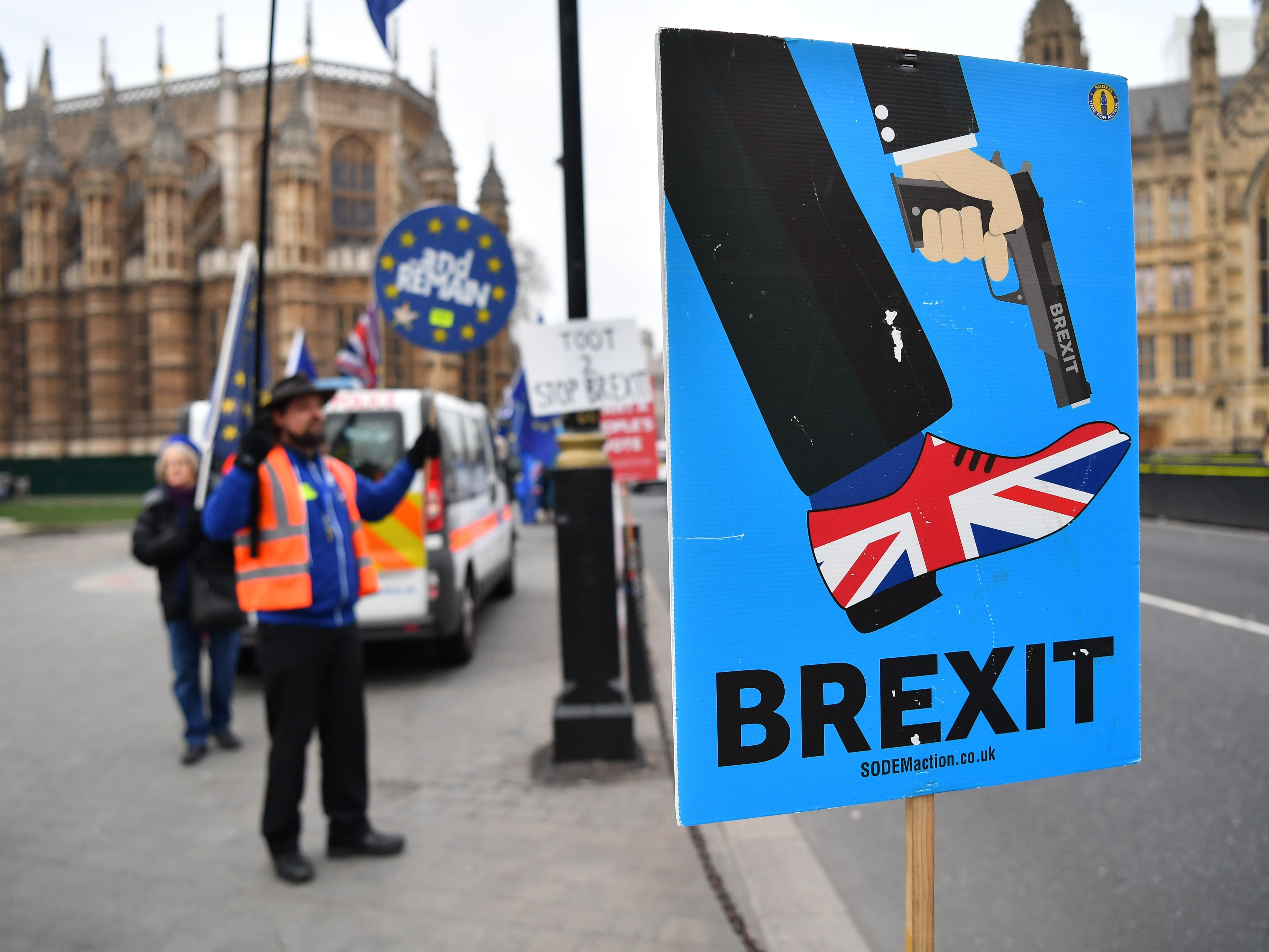 An anti-Brexit protester holds a placard showing a graphic of a person shooting them self in the foot, with the shoe on that foot decorated in the colors of the Union Flag, outside the Houses of Parliament in London on Jan. 10, 2019.