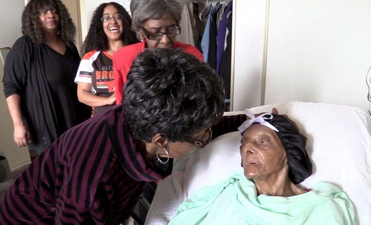 FILE - In this Sept. 22, 2018 file photo, Lessie Brown, right, is visited by her daughters, Verline Wilson, foreground, and Vivian Hatcher, third from left, and other family and friends at her home in Cleveland Heights, Ohio.