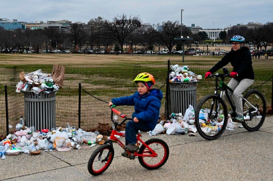 The White House is seen in the background as people bike past uncollected trash on the National Mall, due to the partial government shutdown on Jan. 2, 2019 in Washington, DC.